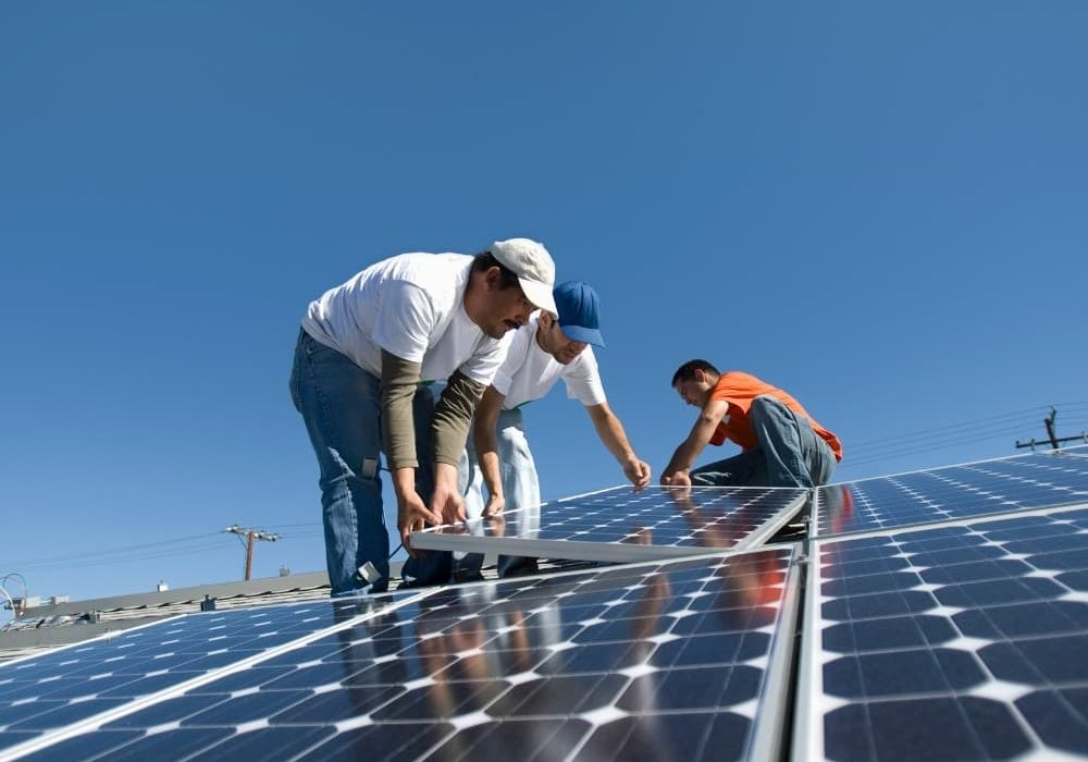 an image of three people installing a solar panel
