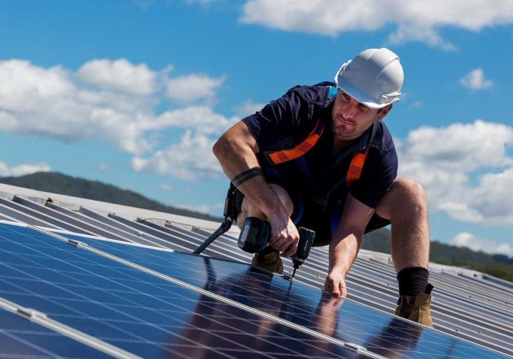 a picture of a man installing a solar panel