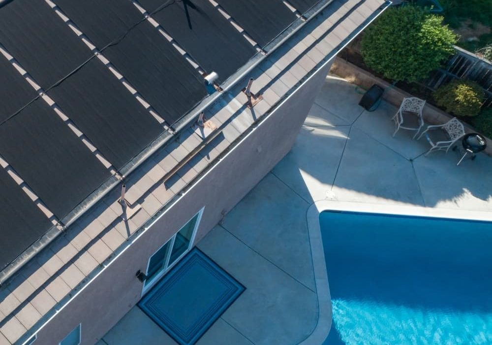 an image of a house installed with solar panel beside a swimming pool